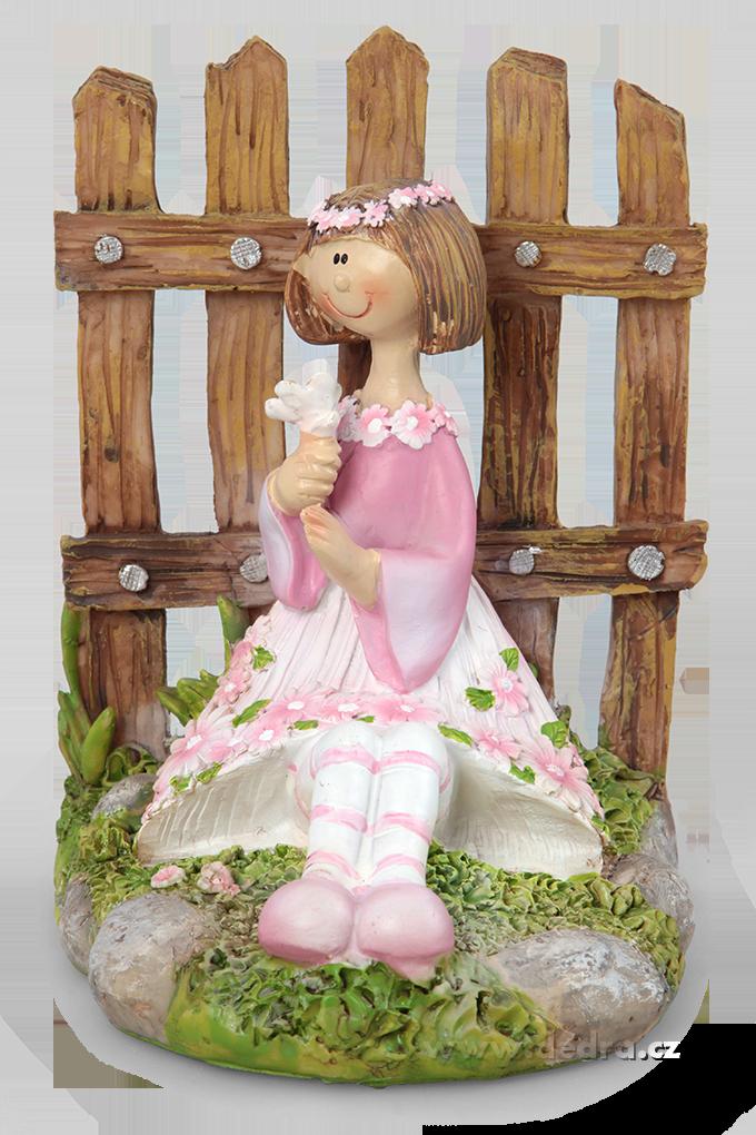 Květinová panenka s kytkou zády k plotu