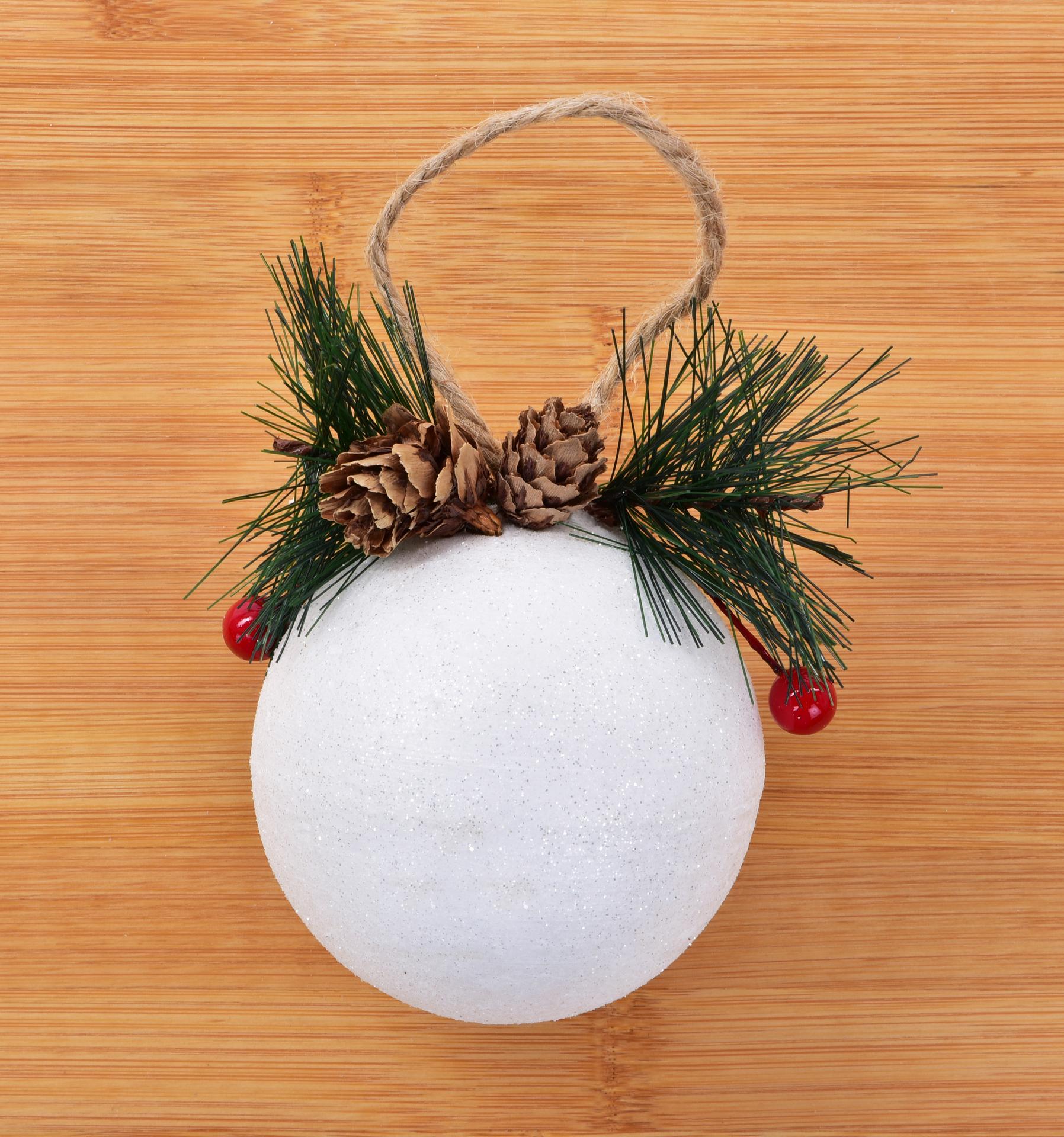 Bílá vánoční koule se šiškou a zelenou větvičkou